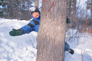 Boy behind tree in snow